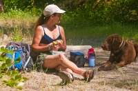 DH-0589 Woman eating her picnic lunch, while her dog politely begs for a bite, North Fork of the American River, Weimar, California.