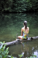 Rural Auburn, California Woman sitting on a log at a quiet swimming hole, near Auburn, California